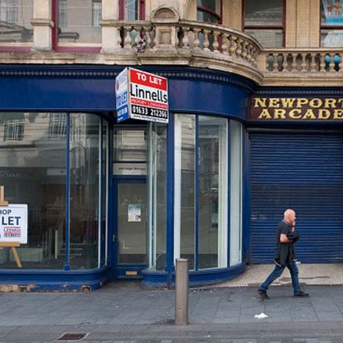 A man walks by an empty storefront