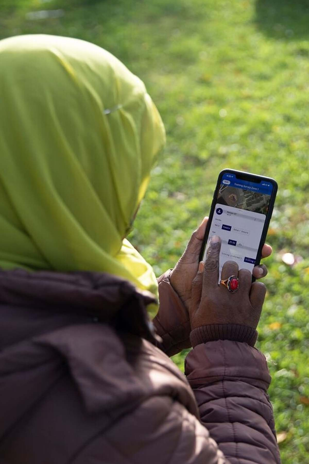 A woman in a hijab looks at her phone
