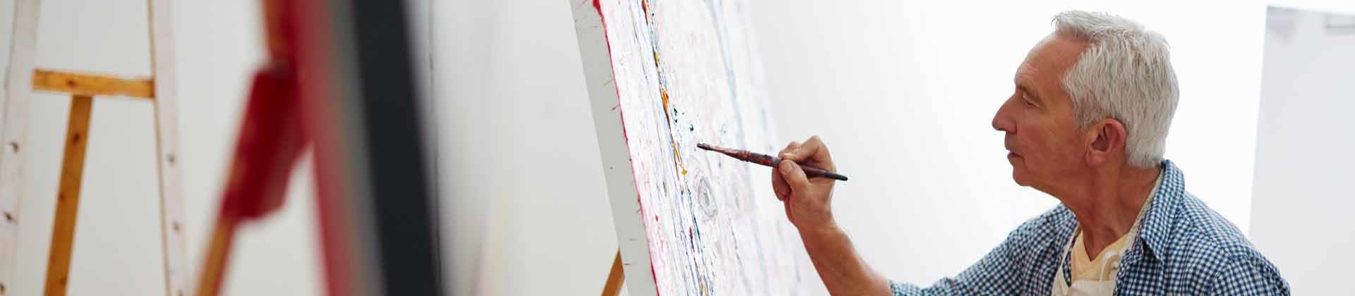 A senior man painting a large canvas