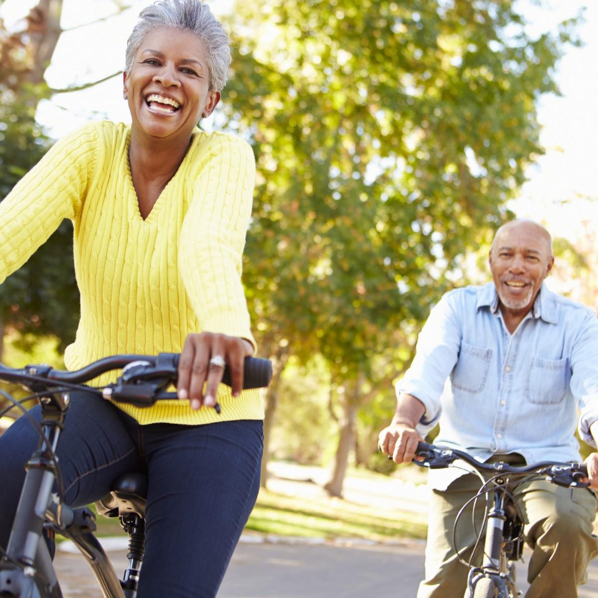 senior couple riding bikes outside a retirement community