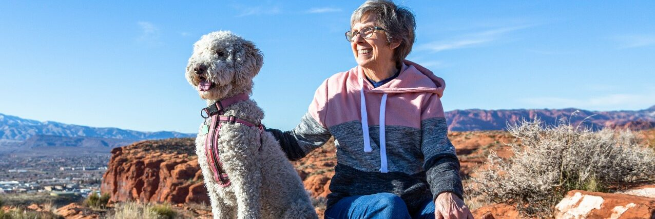 Senior woman sitting on a rock with her dog on a desert mountain