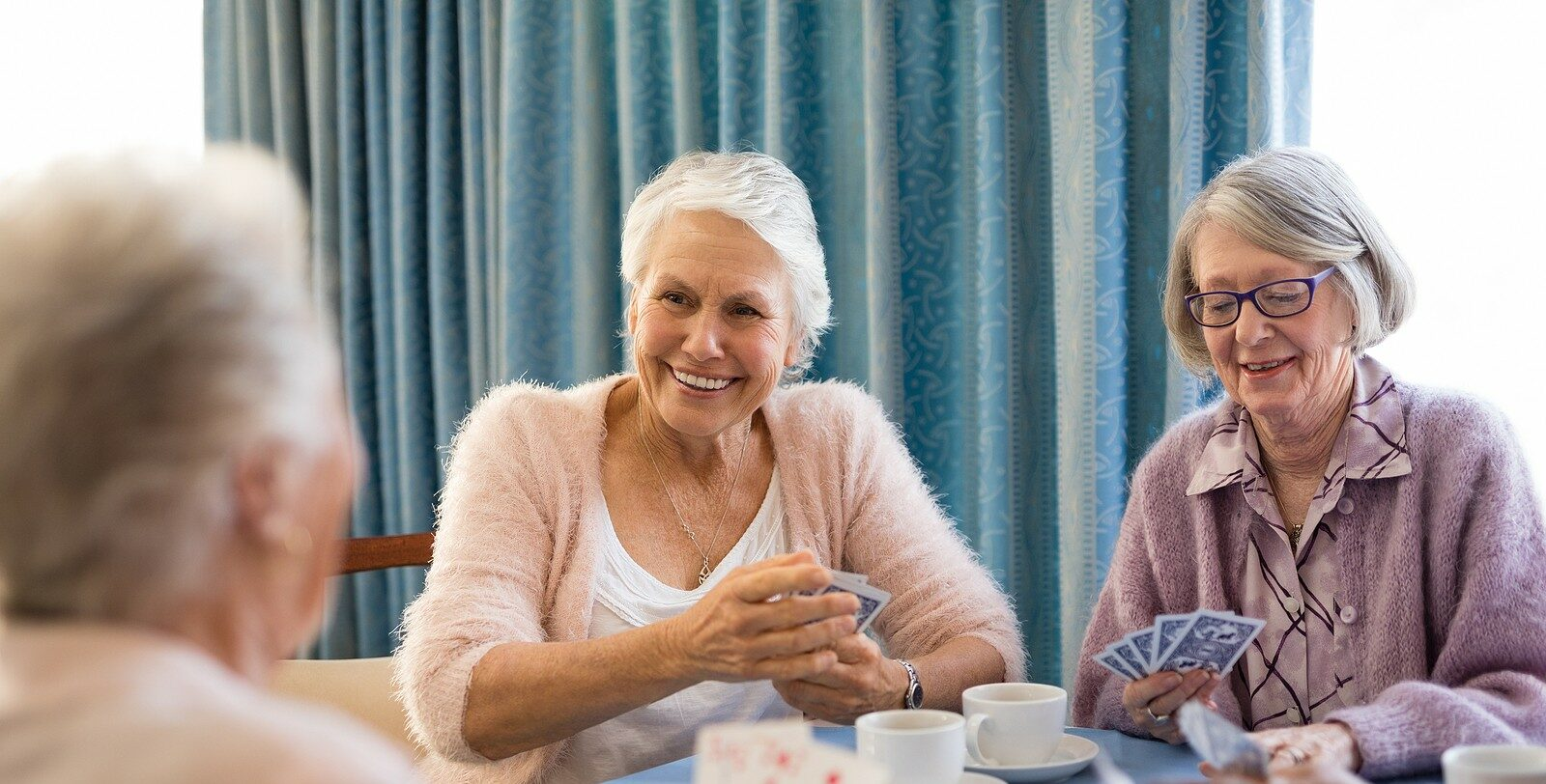 Group of seniors talking together in a senior living community.