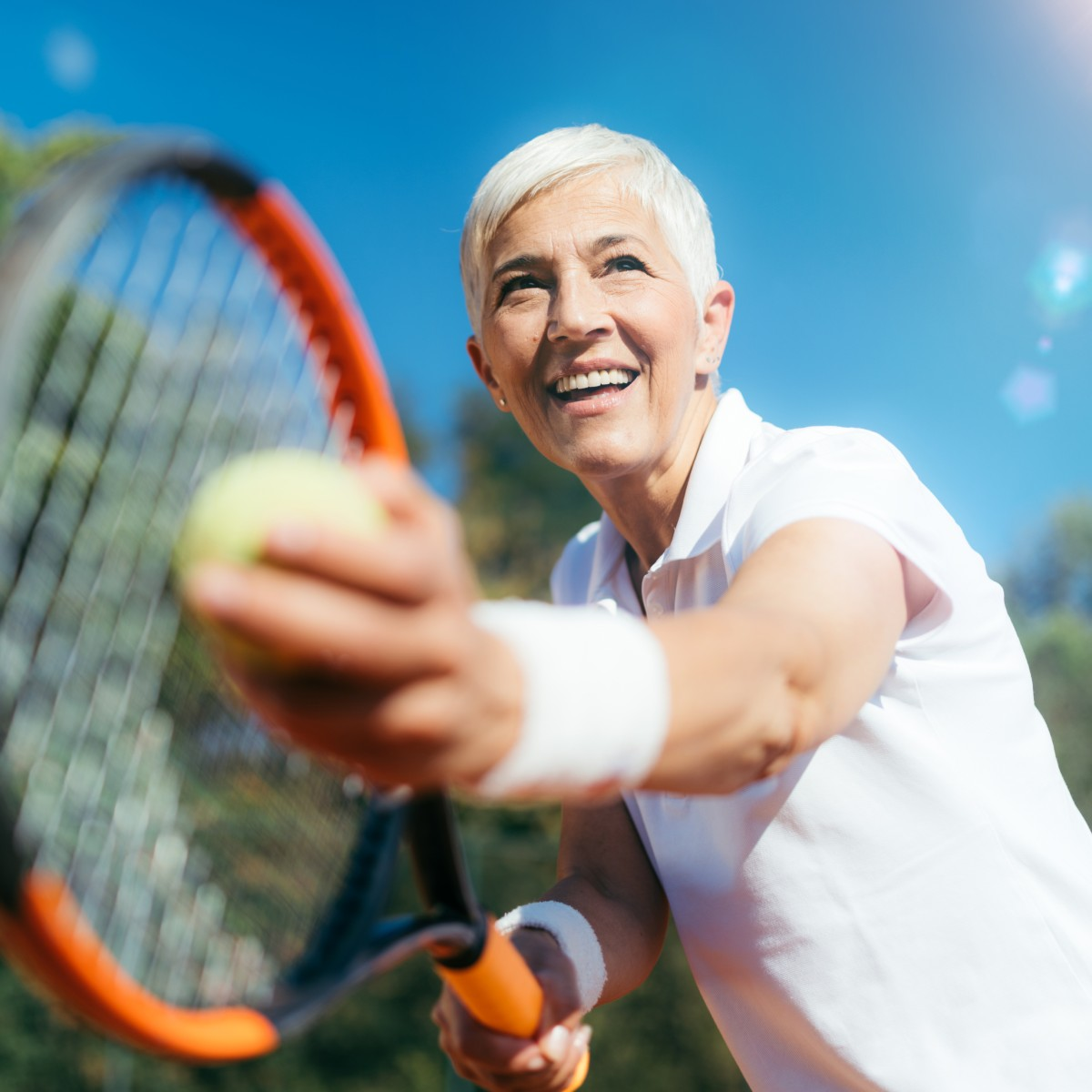 senior lady playing tennis at an independent living community in Peoria, AZ