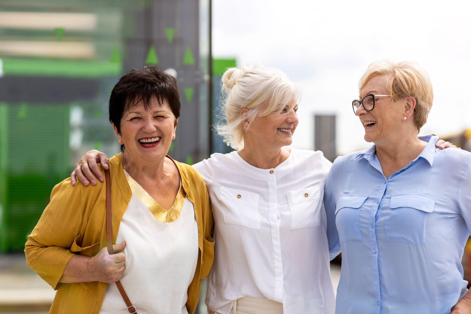 Three female seniors stand together and laugh