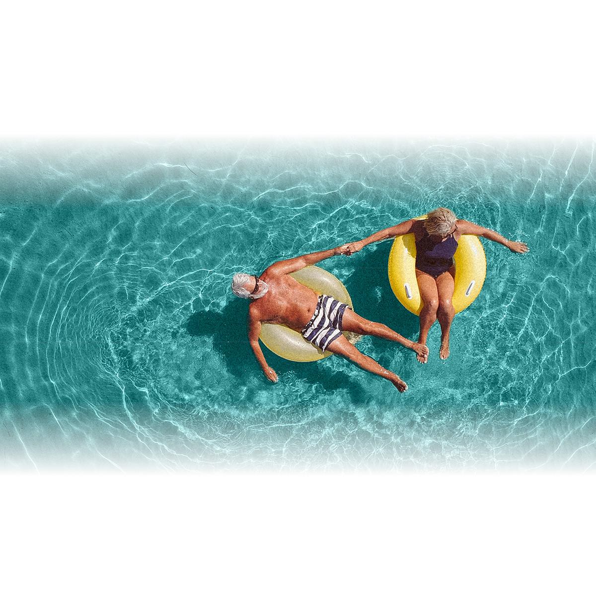 Senior couple enjoying pool at retirement community