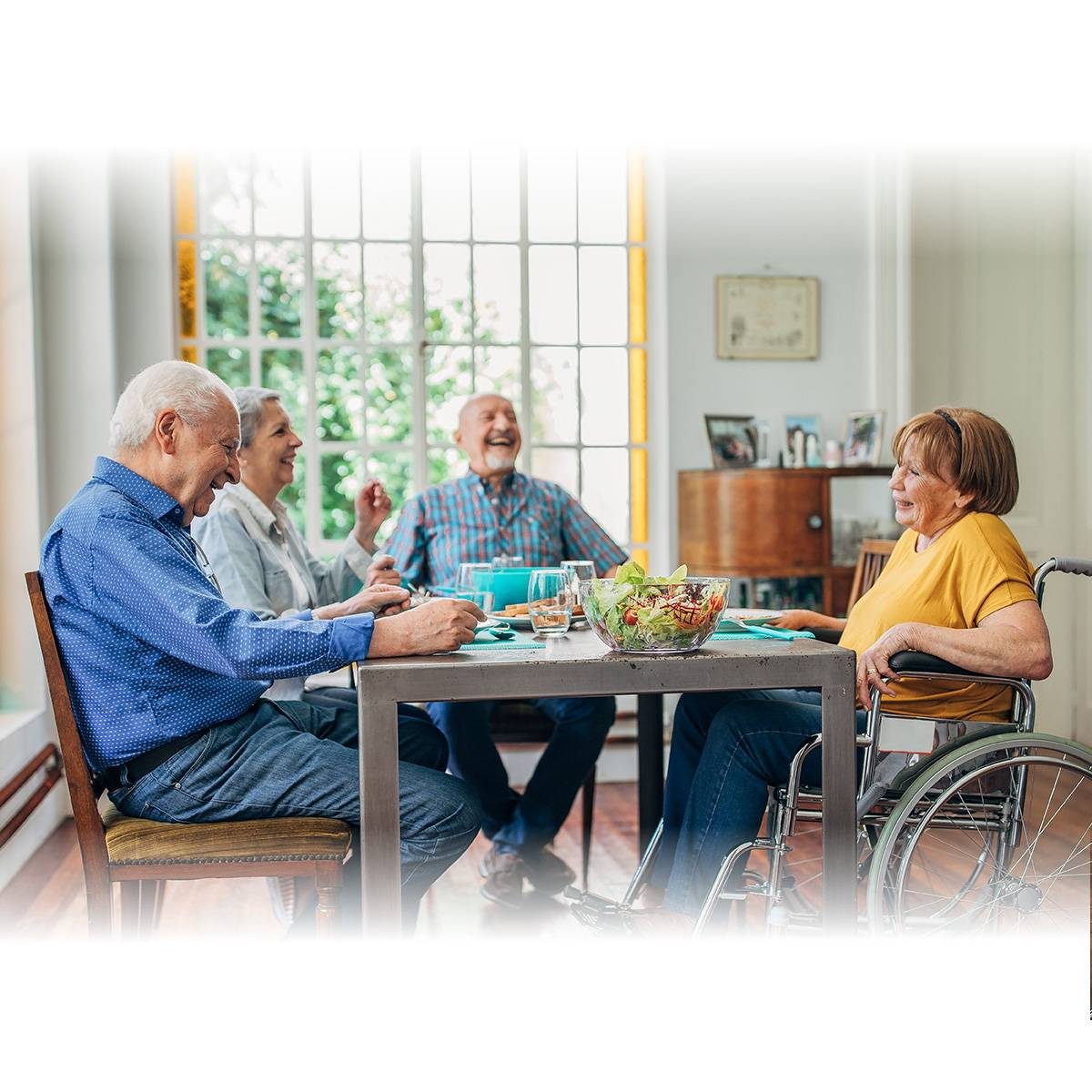 A group of seniors sit around a table in a dining room