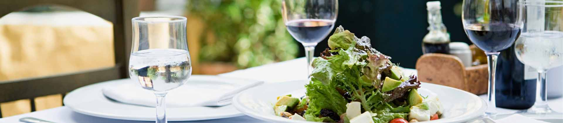 A close up photo of a plated salad with a glass of red wine and a glass of water