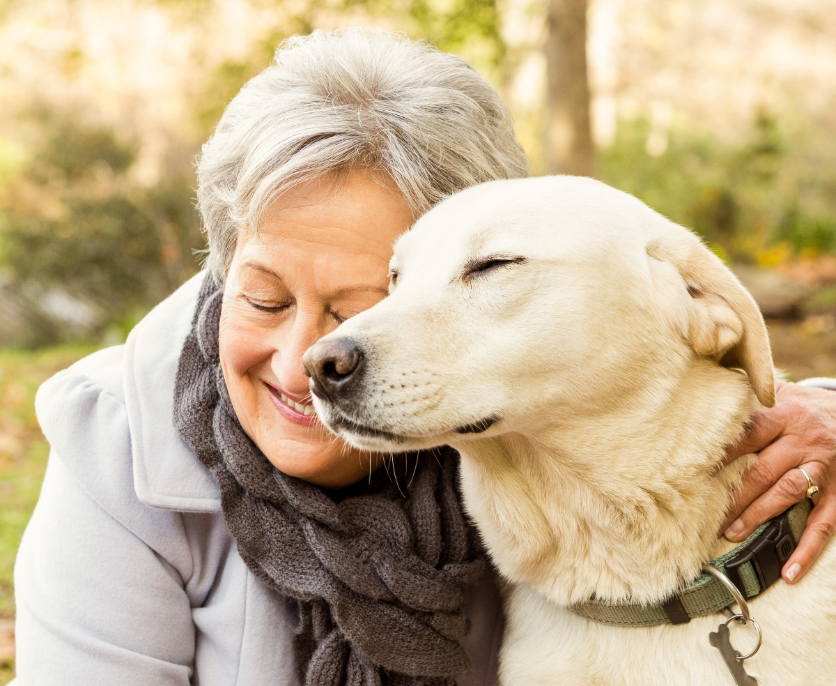 senior woman hugging her golden retriever