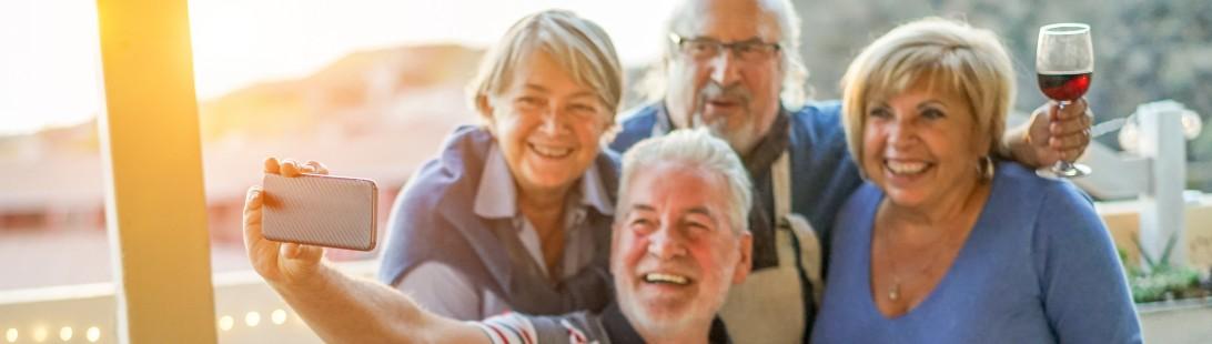 Senior friends, couple socializing during dinner, taking selfie