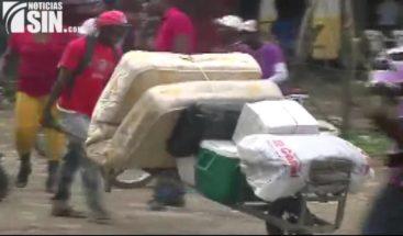 Con sus pertenencias en mano haitianos cruzan la frontera hacia Haití