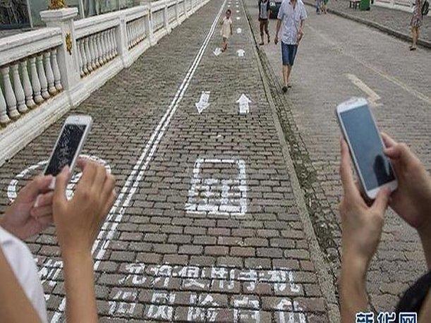 Una ciudad china crea un carril exclusivo para peatones que miran al móvil