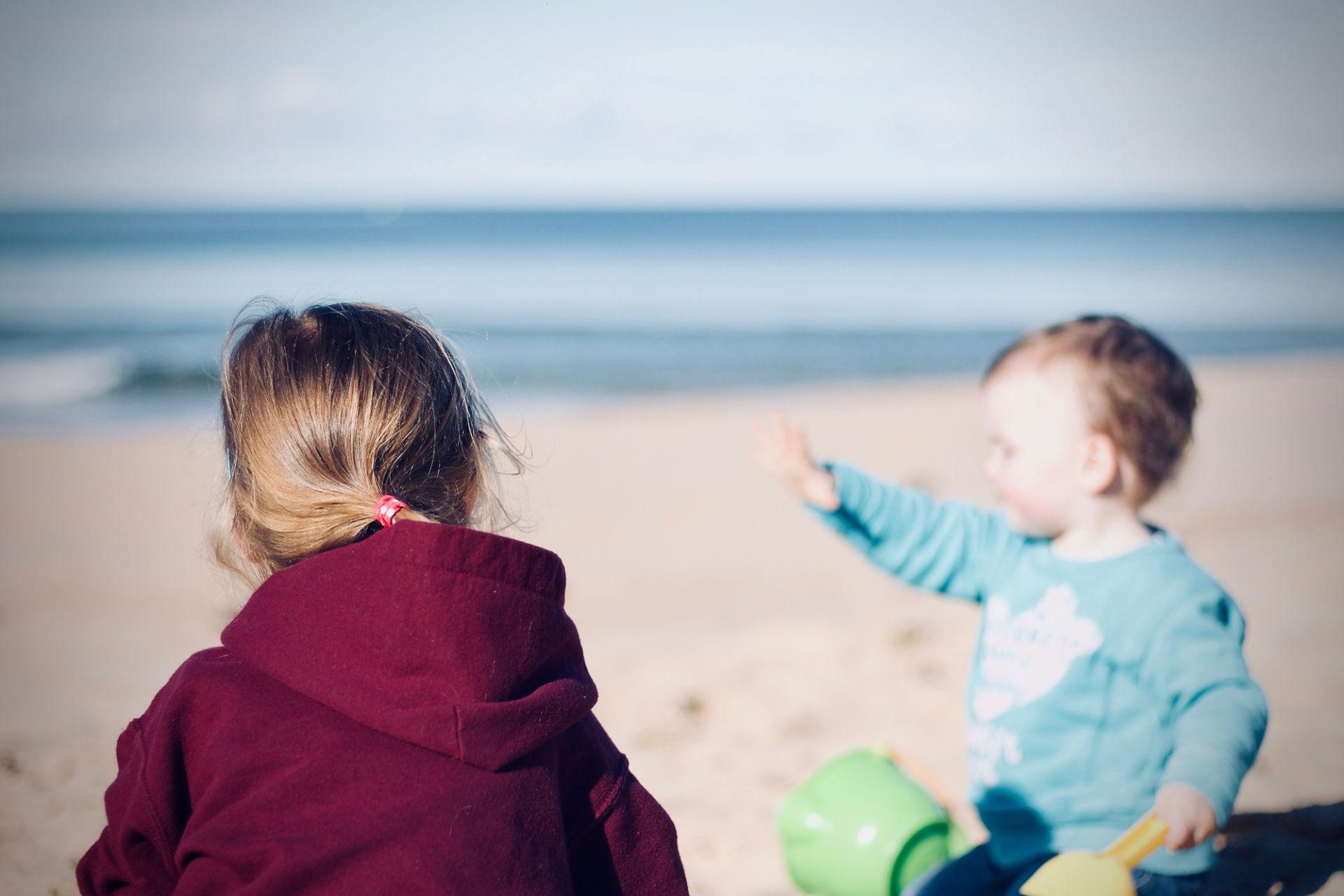 Nainen ja lapsi rannalla selin kameraan.