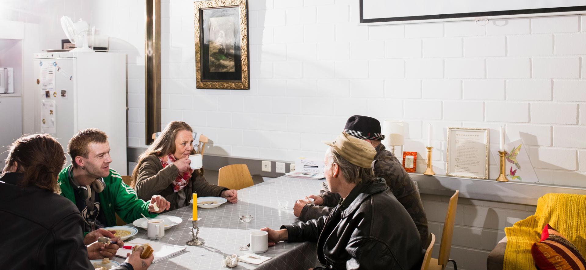 Ihmisiä yhdessä pöydän ääressä