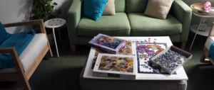 Kaksi nojatuolia ja sohvapöytä, jonka päällä palapelejä.