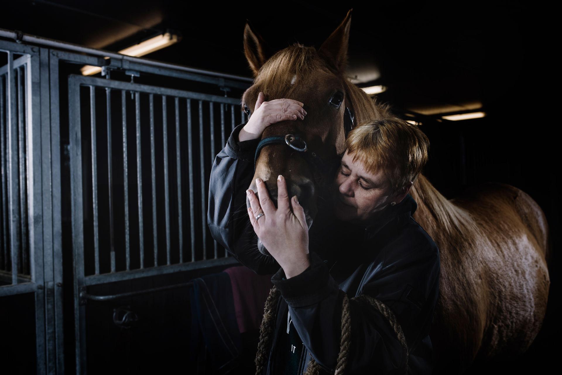 Nainen halaa hevosta.