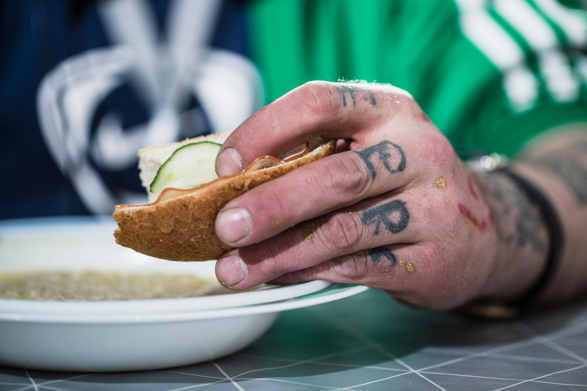Lähikuva kädestä soppalautasen päällä, pitelee leipää.