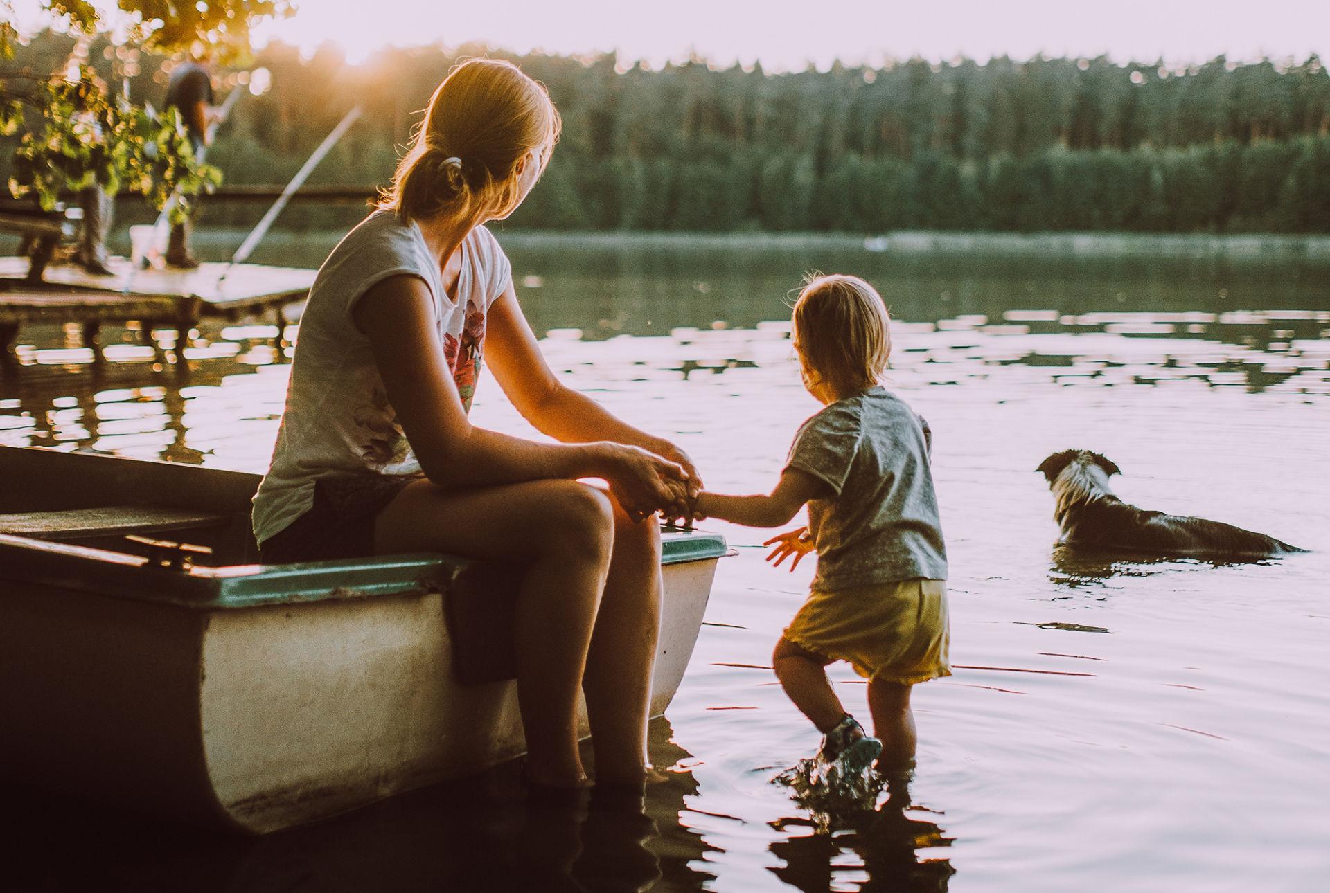 Nainen ja lapsi järven rannalla. Nainen istuu veneen päällä ja pitää lasta kädestä kiinni. PIdemmällä vedessä seisoo koira. Kaikki ovat selin katsojaan. On auringonlaskun aika.