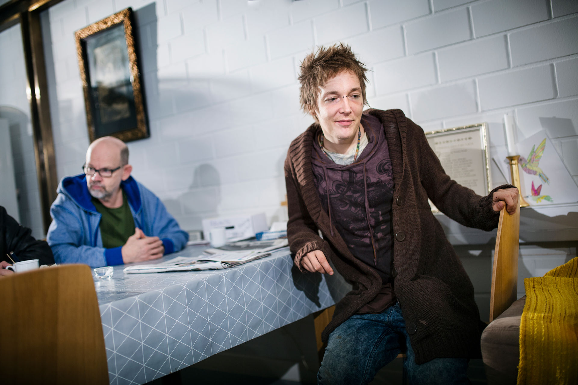 Nuori mies istuu pöydän ääressä päiväkeskuksessa.
