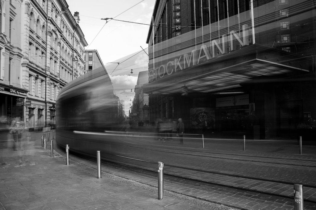 Raitiovaunu ohittaa Stokcmannin tavaratalon. Kuva on otettu pitkällä sulkjiajalla, joten raitiovaunun liike näkyy usvaisina viivoina.