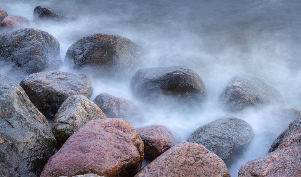 Isoja kiviä rannalla. Kuva on otettu pitkällä suljinajalla, joten vesipisarat näyttävät sumulta.
