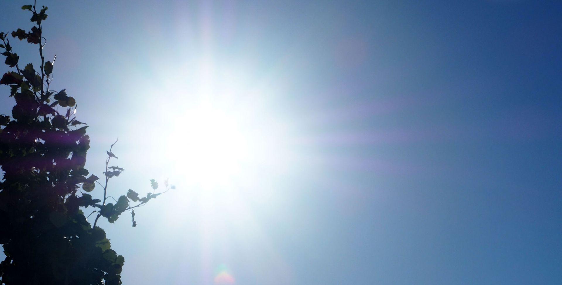 Kirkkaana loistava aurinko sinisellä taivaalla.