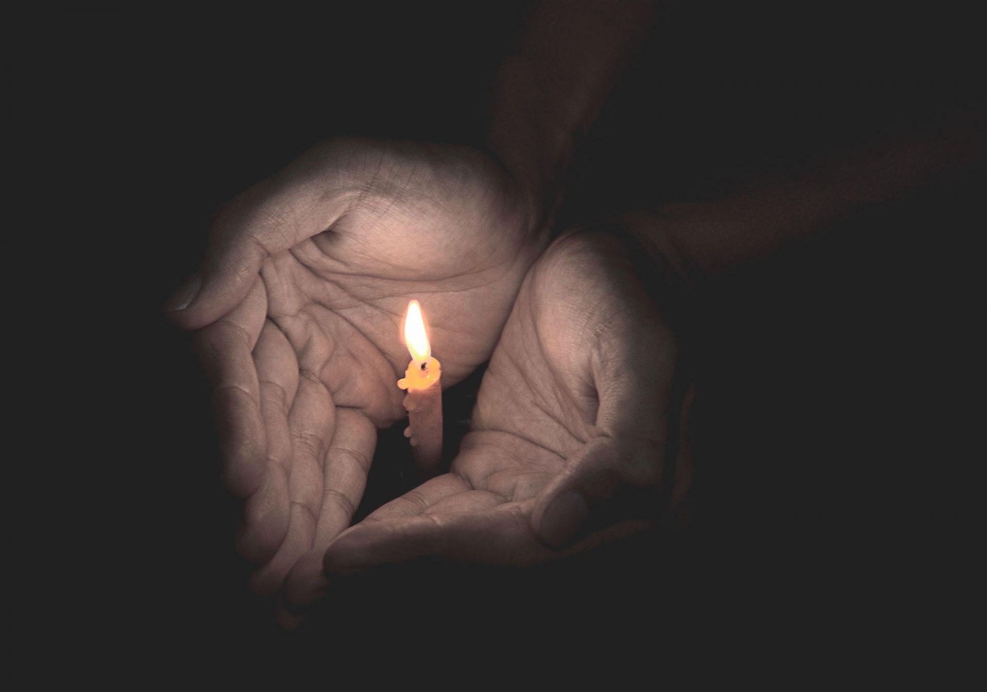 Kämmenet, joiden keskellä pieni sytytetty kynttilä.