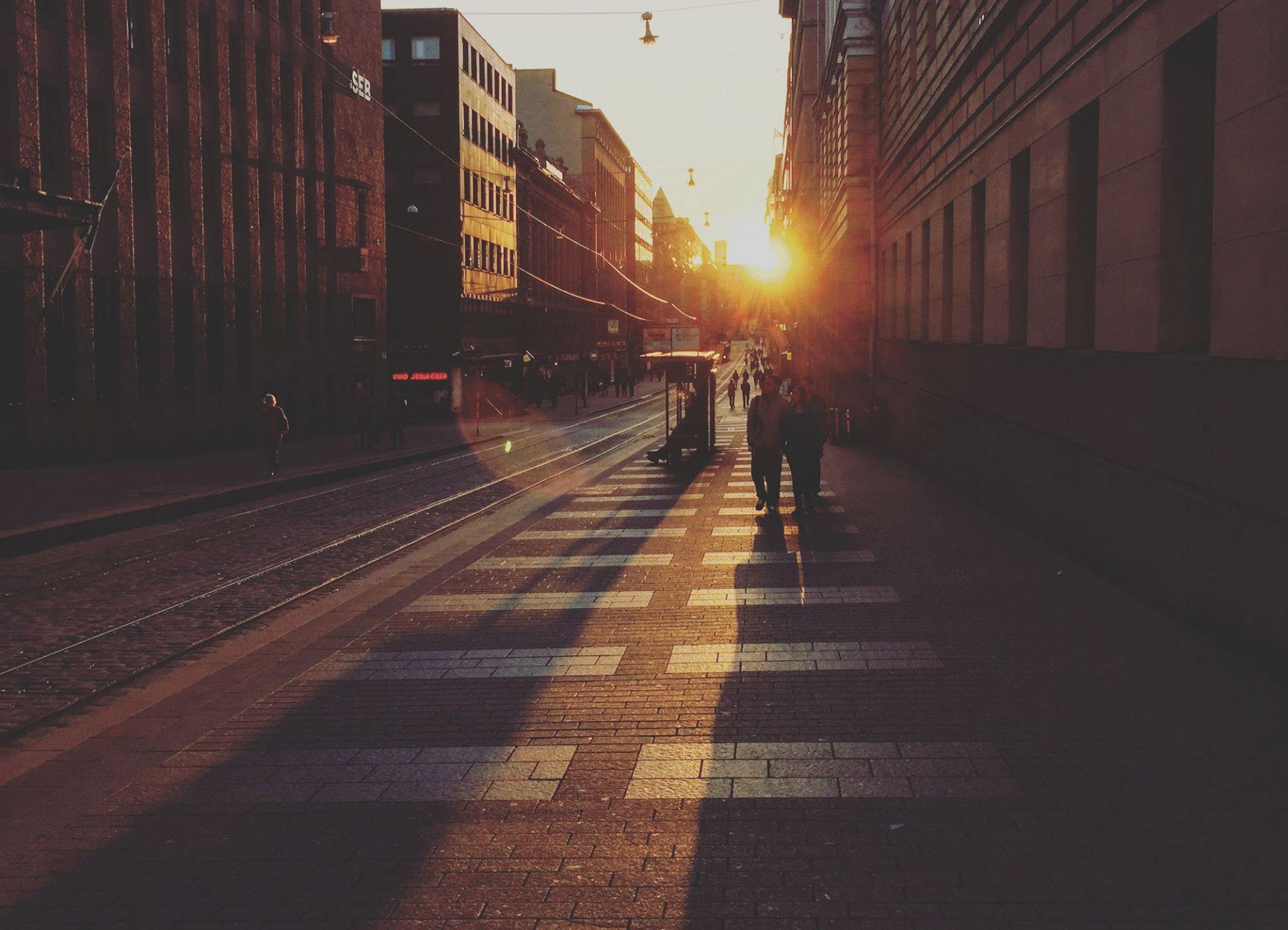 Ihmisisä kävelemässä Aleksanterinkadulla auringonlaskun aikaan.