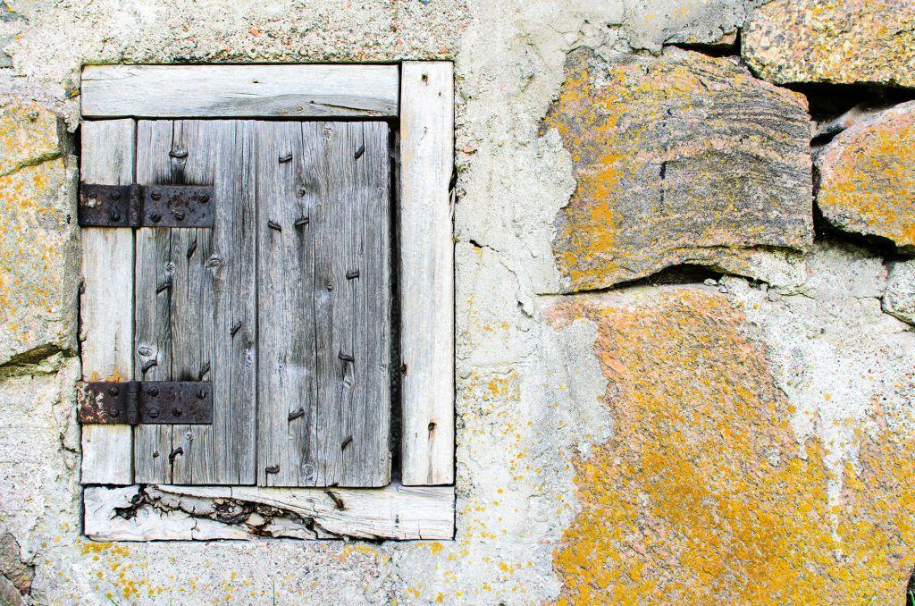 Vanha luukun ovi kuluneessa keltaisessa kiviseinässä.