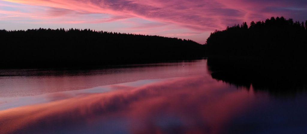 Auringonlasku suomalaisessa järvimaisemassa.