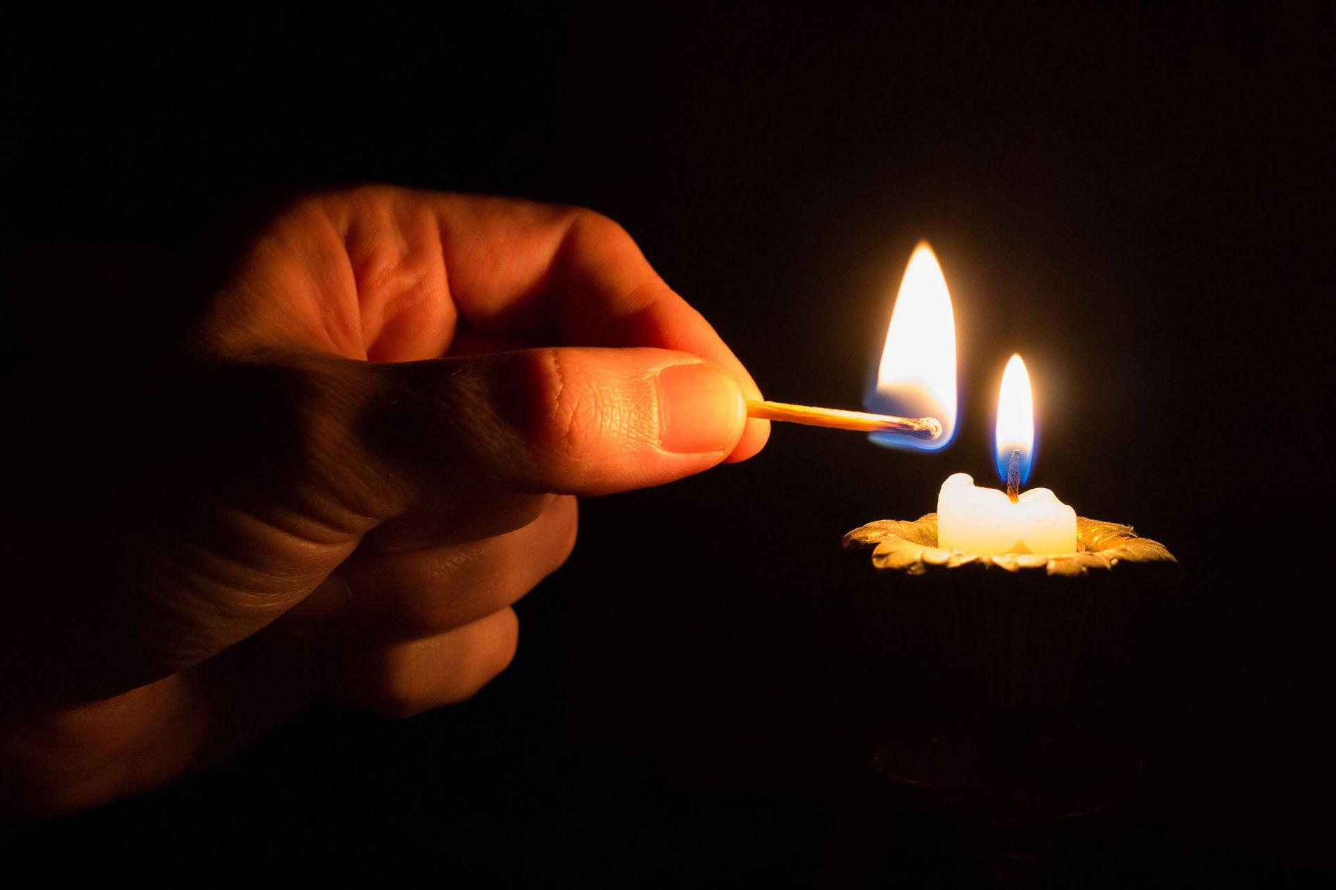 Ihminen sytyttää kynttilän, tiukasti rajatussa kuvassa vain käsi, tulitikku ja kynttilä, missä jo liekki.