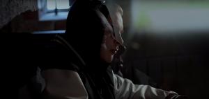 Pysäytyskuva Ville Nurmisen musiikkivideolta. Kasvot hämärässä tilassa.