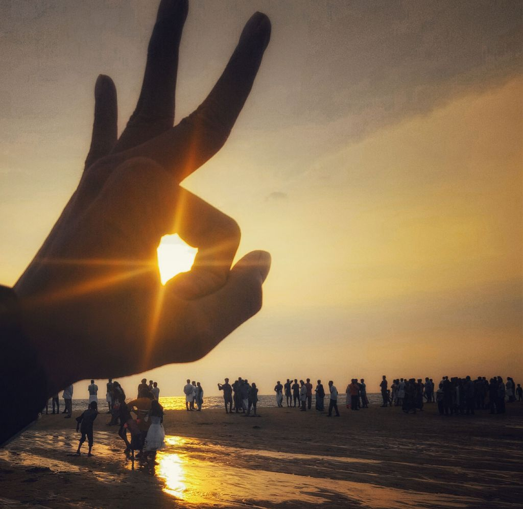 Aurinko paistaa ympyrään asetettujen sormien läpi rannalla.