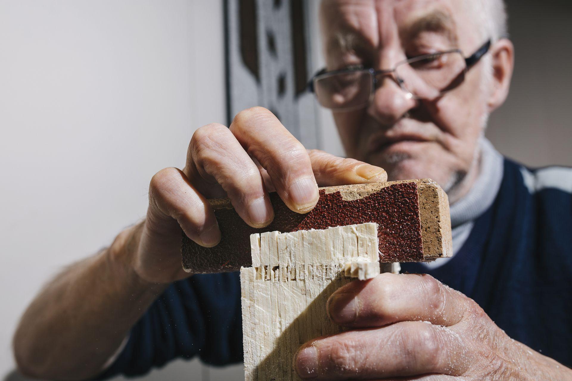 Mies hioo yhteenliimatuista tulitikuista tehtyä levyä.
