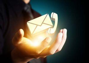 Kuvassa on avoin valaistu kämmen, jonka päällä ilmassa kelluu sähköpostin symbolina kirjekuori ja puhelinsoiton symbolina puhelimen kuuloke.
