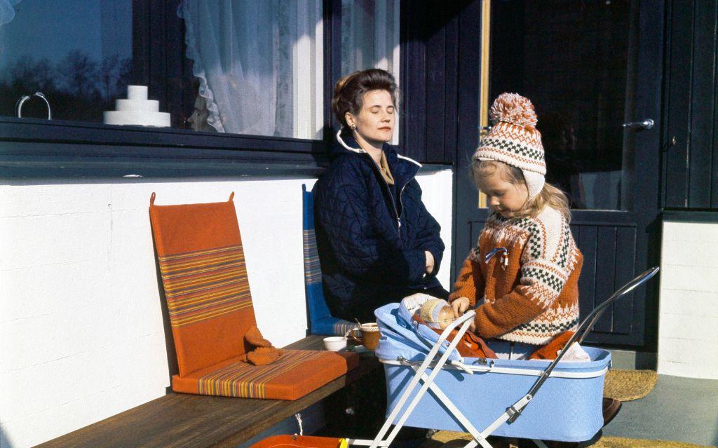 Äiti ja tytär parvekkeella 1960-luvulla. Äiti nojaa istuen seinään silmät kiinni, tytär leikkii nukella, joka on nukenvaunuissa.