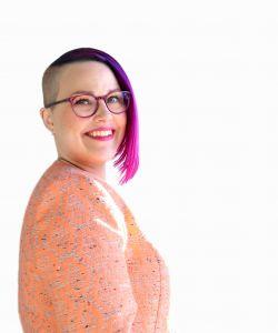 Kuvassa on silmälasipäinen Riikka Niemi, jolla on toiselta puolen päätä hiukset aivan lyhyet ja toiselta puolen pidemmät.