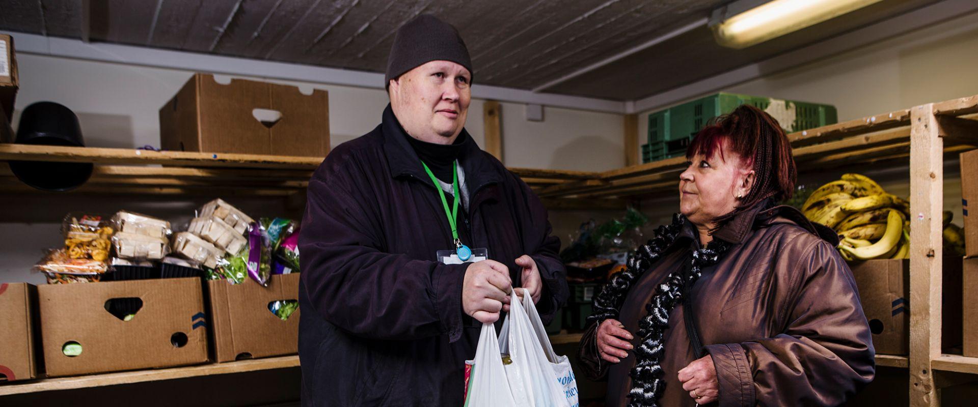 Mies ja nainen lajittelevat ruokaa ruoka-apupisteessä Hyvinkään Toimari ry:ssä.