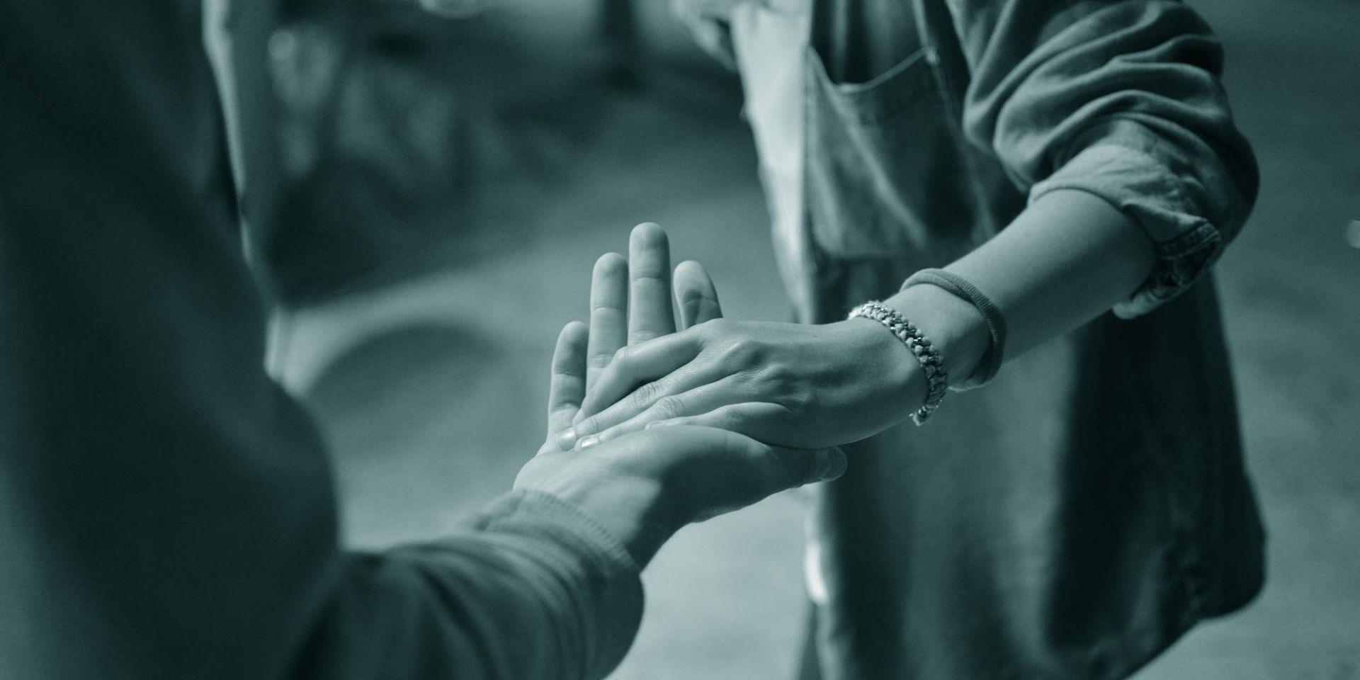 Kaksi ihmistä pitää toisiaan käsistä kiinni.
