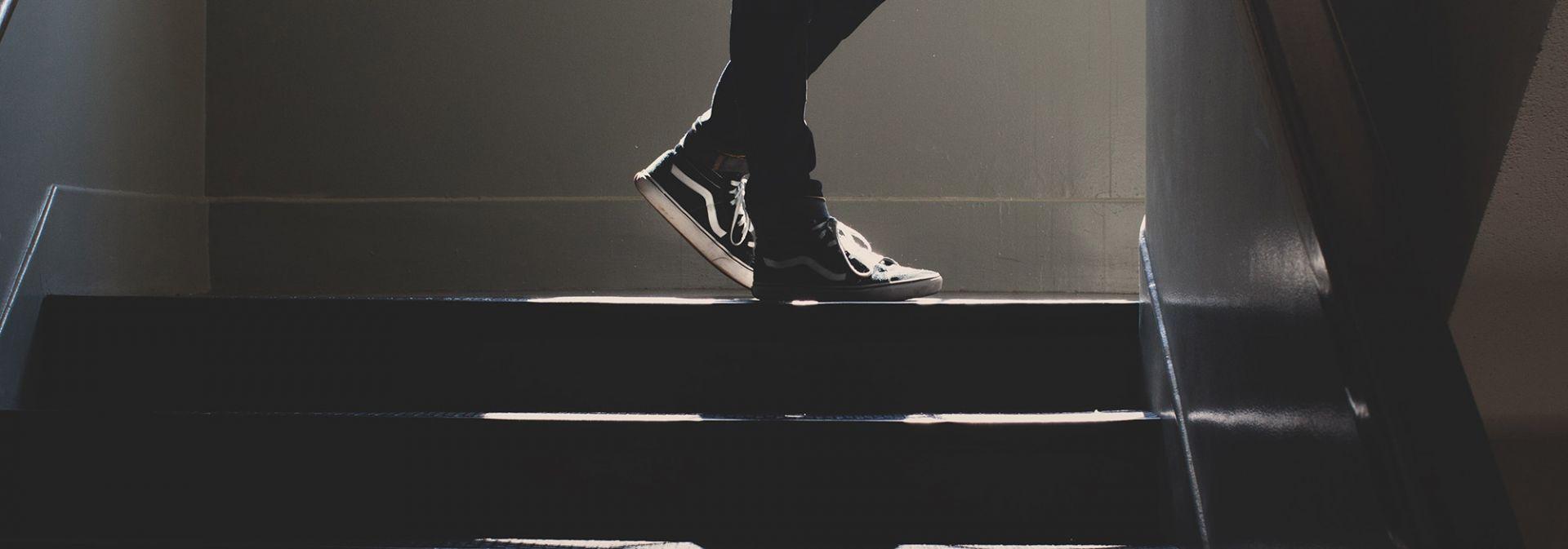 Ihminen seisoo rappukäytävässä, kuvassa näkyvät vain hänen tennarinsa. Taustalta lankeaa voimakas valo.