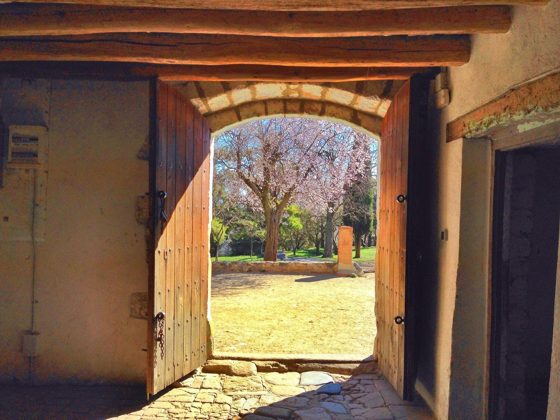 Vanhan rakennuksen oviaukko, josta paistaa aurinko.