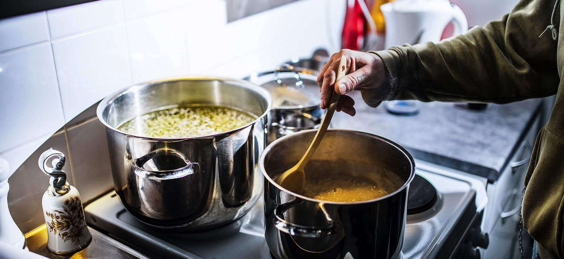 Hernesopan keittoa. Kuvassa näkyy kaksi kattilaa ja käsi joka hämmentää keittoa. Käsi on tatuoitu. Kuva on otettu Sininauhaliiton jäsenyhteisössä Vihreässä Keitaassa Helsingissä.