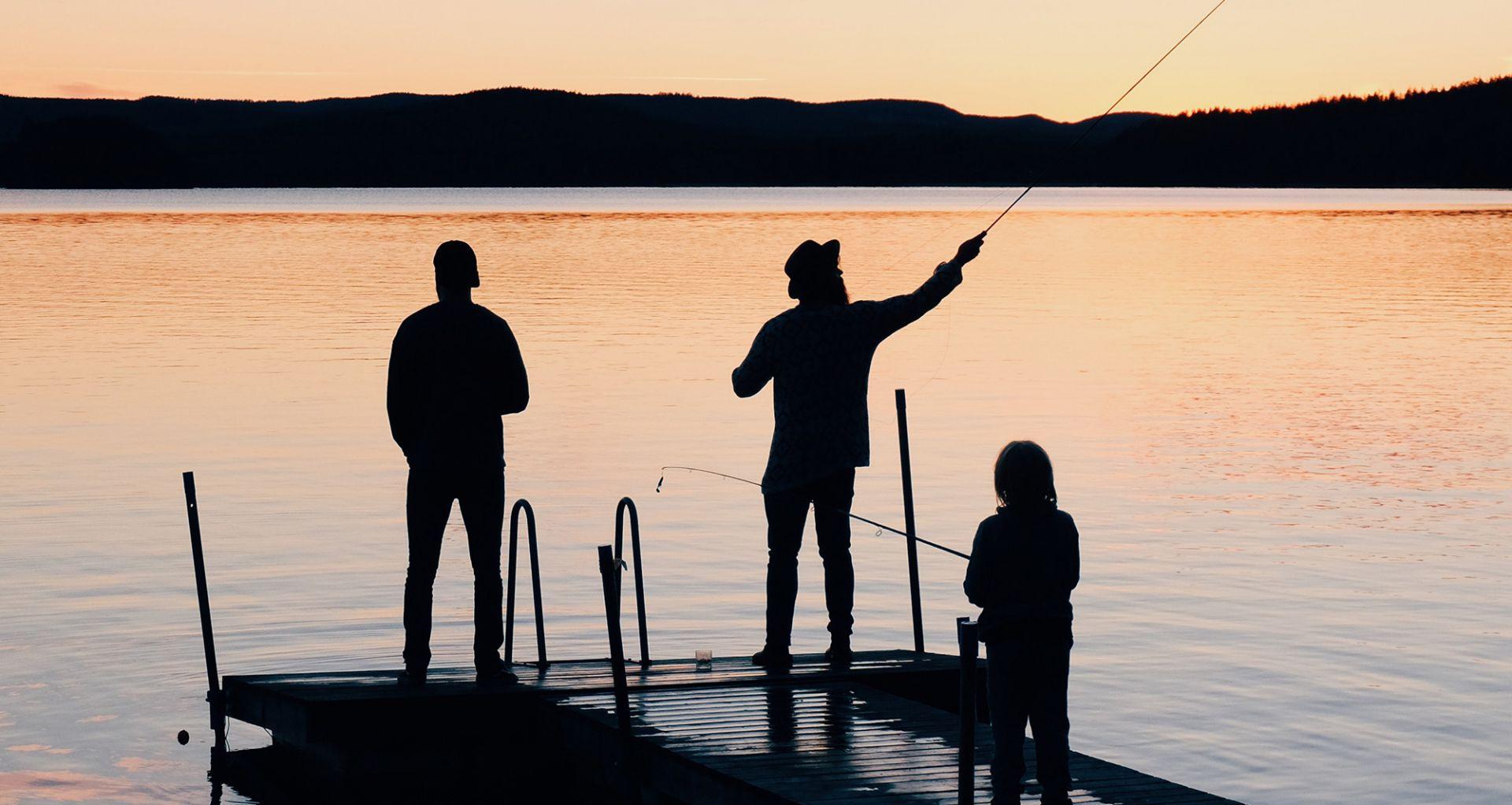 Kolme ihmistä laiturilla, yksi heistä onkii. Taustalla auringonlasku.