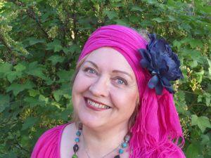 Naurava nainen, jolla on päässään kukkakoristeinen turbaaniksi kiedottu huivi