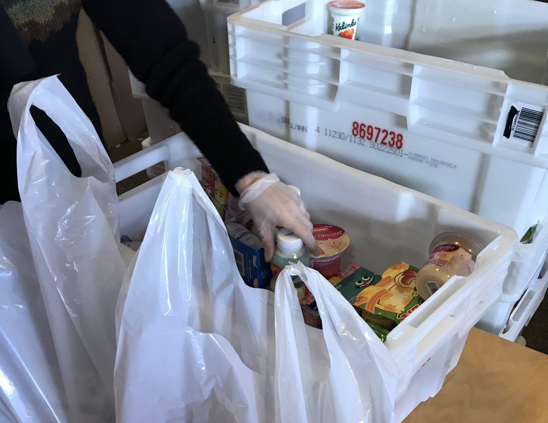 Ruoka-avun lajittelua muovilaatikoista muovipusseihin. Henkilöllä muovihansikkaat kädessä.