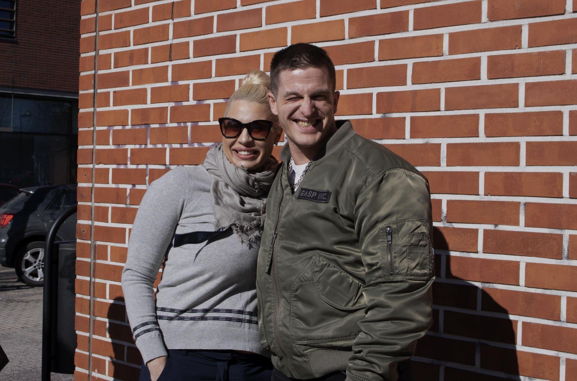 Vasemmalla hymyilevä nuorehko nainen, jolla on aurinkolasit, ja oikealla pitkä, nuorehko mies, joka virnistää kohti.