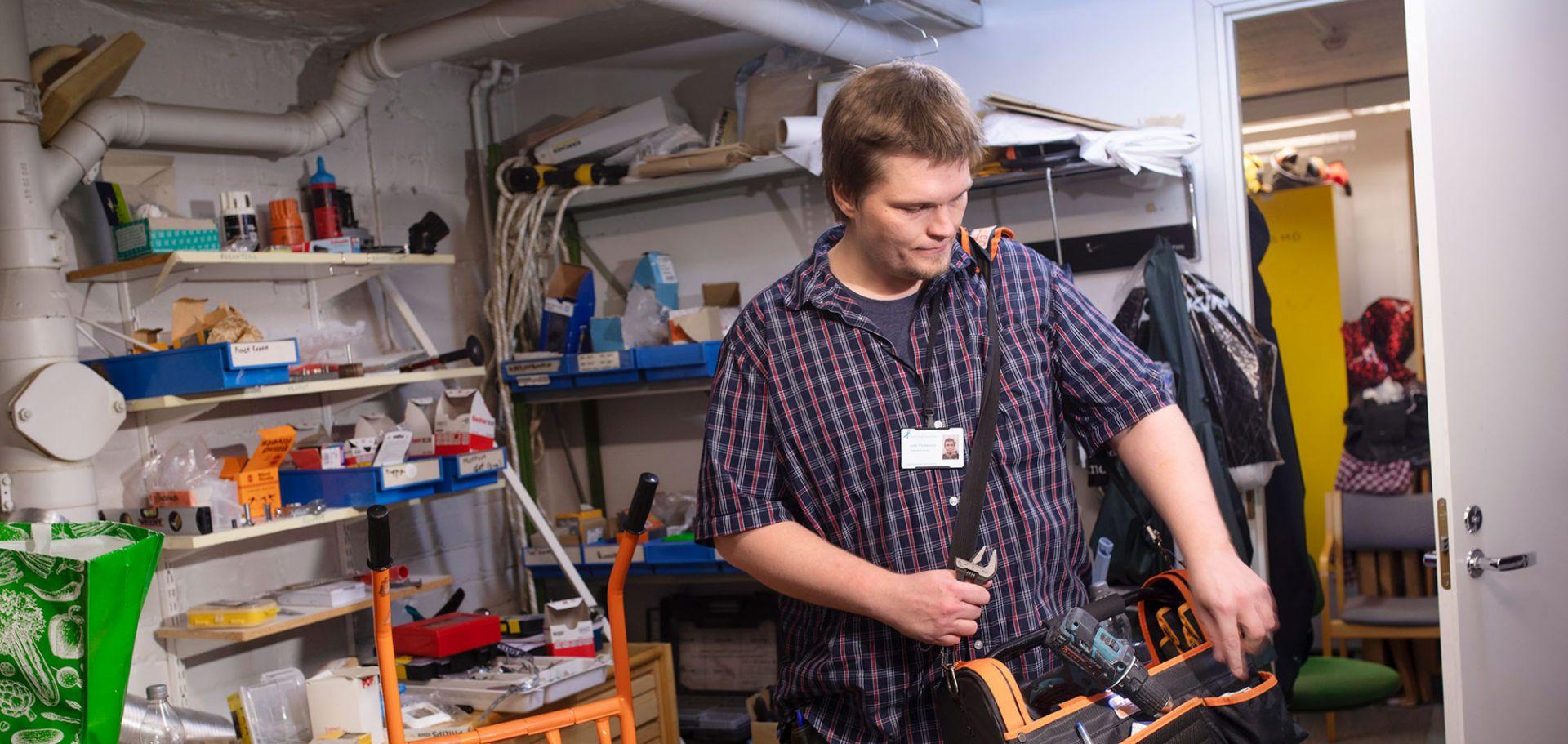 Mies kantaa olalla työkalulaatikkoa. Hän on varastossa.