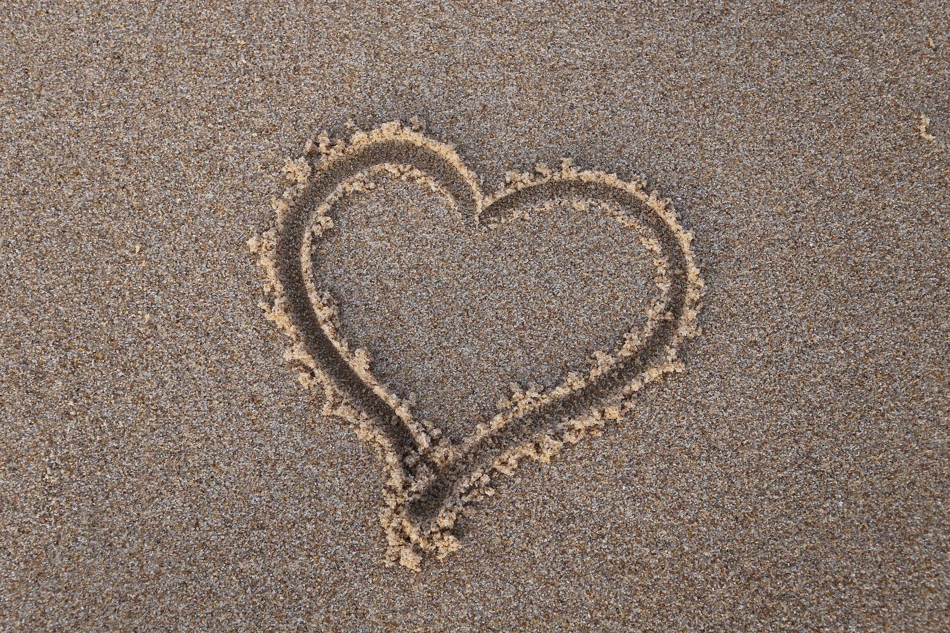 Hiekkaan piirretty sydän.
