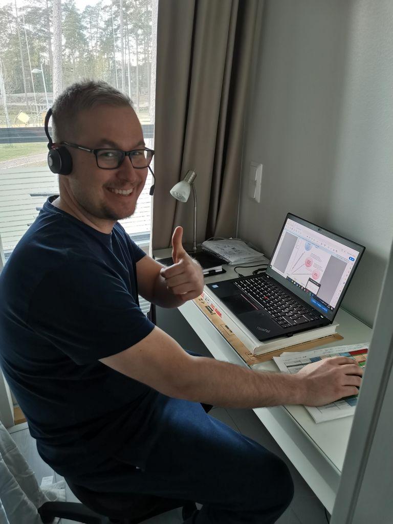 Hymyilevä, silmälasipäinen mies näyttää peukkua ja istuu tietokoneen ääressä kuulokkeet korvillaan.