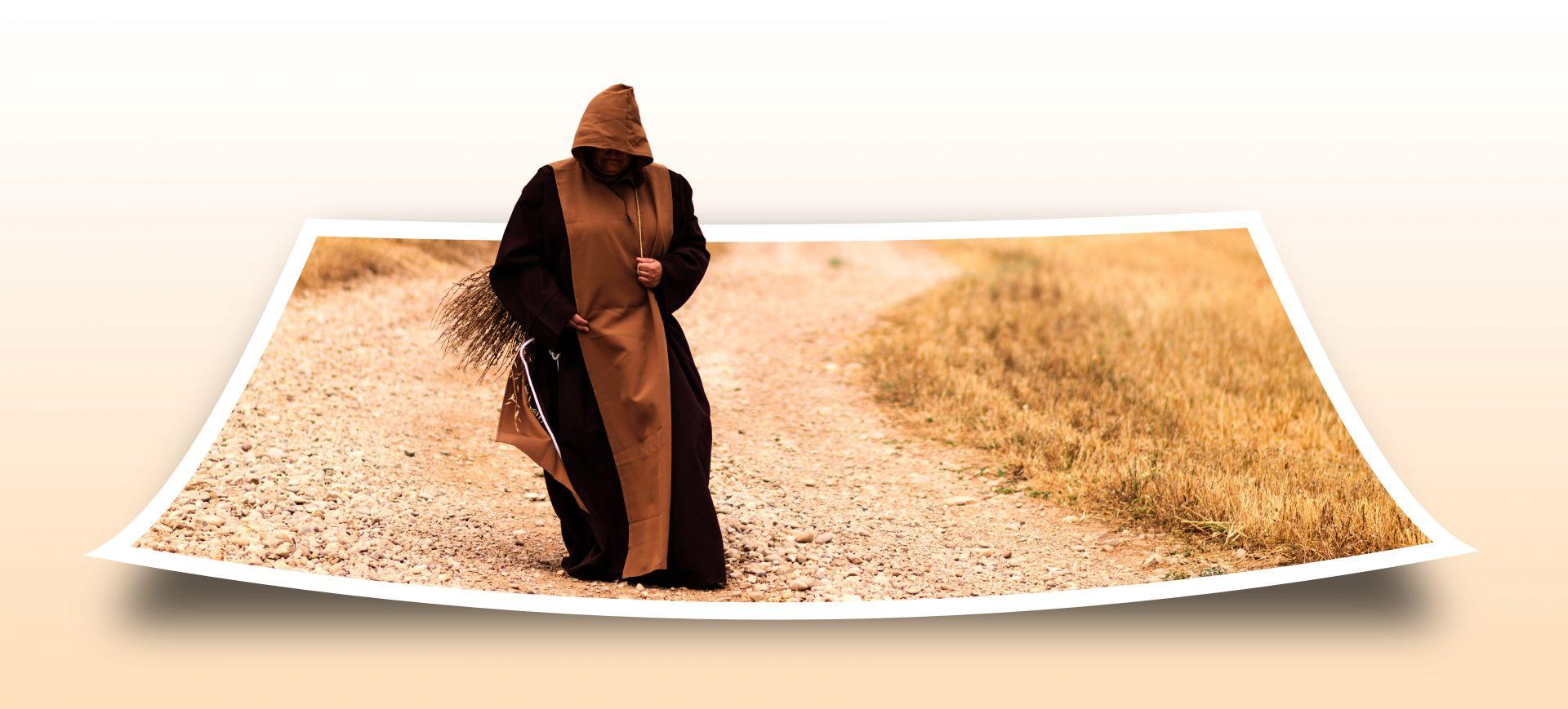 Munkinkaapuinen henkilö kävelee hiekkatietä, joka on valokuva eikä oikea tie.