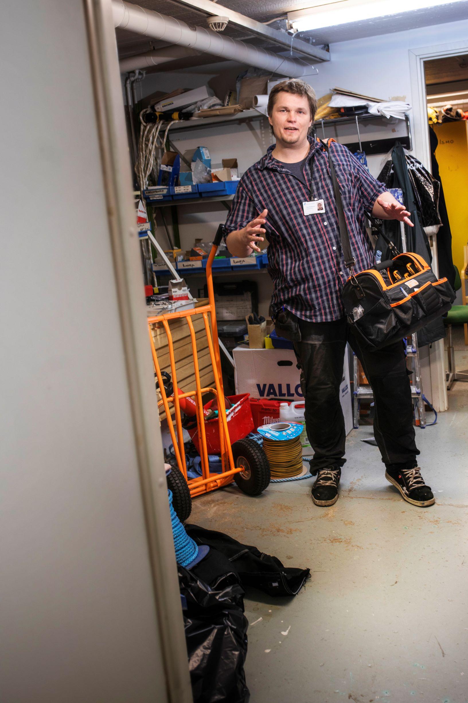 Junnu Parkkonen työhuoneessaan, joka on täynnä työkaluja. Olalla työkalulaukku.